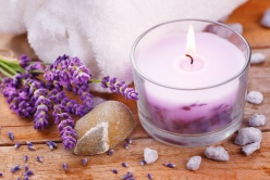 Spa stil life with perfumed candle, white towel, stones and lavender flowers